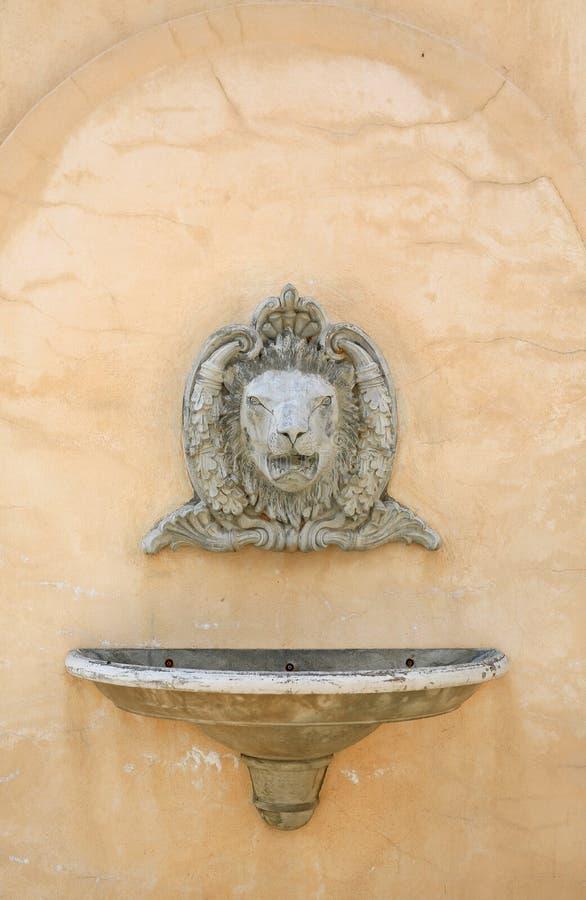 Lavabo antique avec un évier lapidé de tête et de navire de lion sur le mur en béton image stock