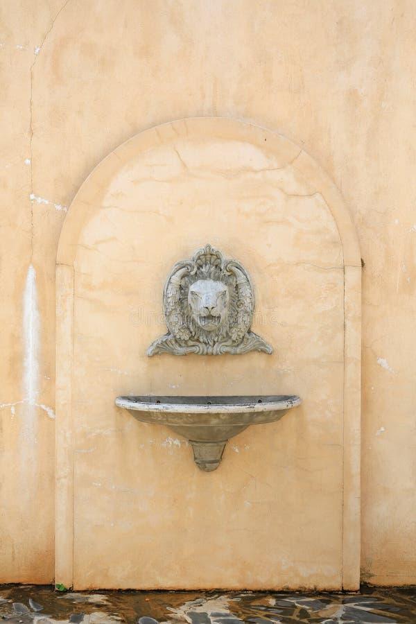 Lavabo antique avec un évier lapidé de tête et de navire de lion sur le mur en béton photos stock