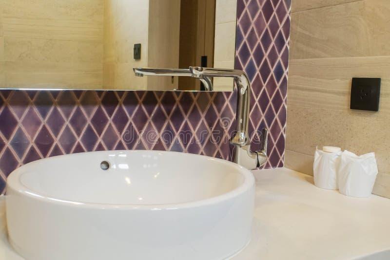 Lavabo ceramico con il rubinetto e lo specchio nel bagno dell'hotel immagini stock libere da diritti