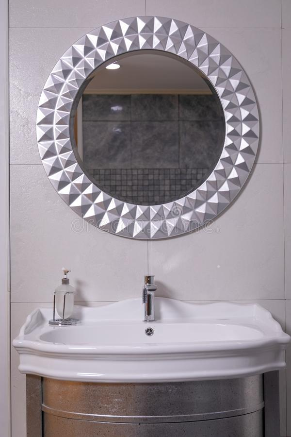 Lavabo de cerámica blanco con los estantes debajo de él y los platos para el jabón líquido, en el fondo del ingenio de mármol bla imagen de archivo