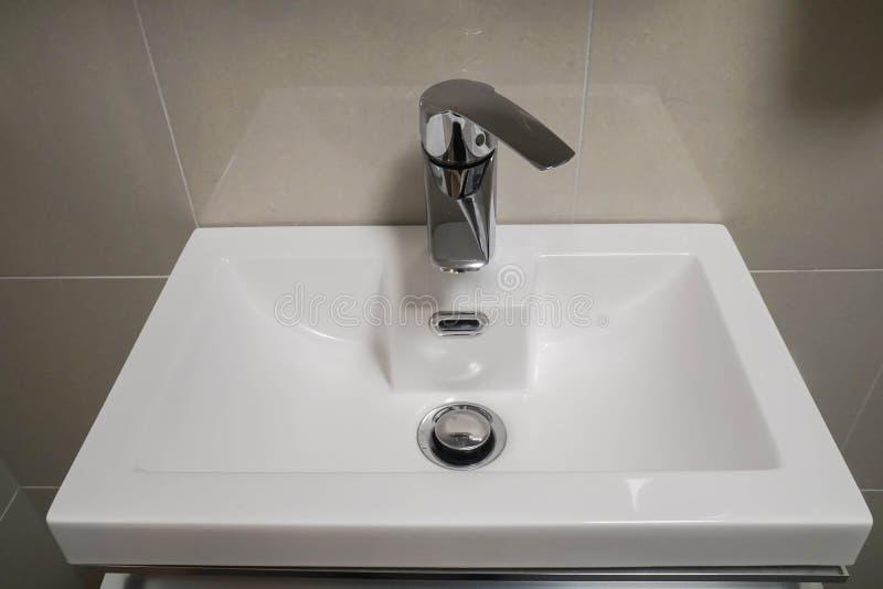 Lavabo de cerámica con el grifo caliente y frío en cuarto de baño del hotel de lujo fotografía de archivo