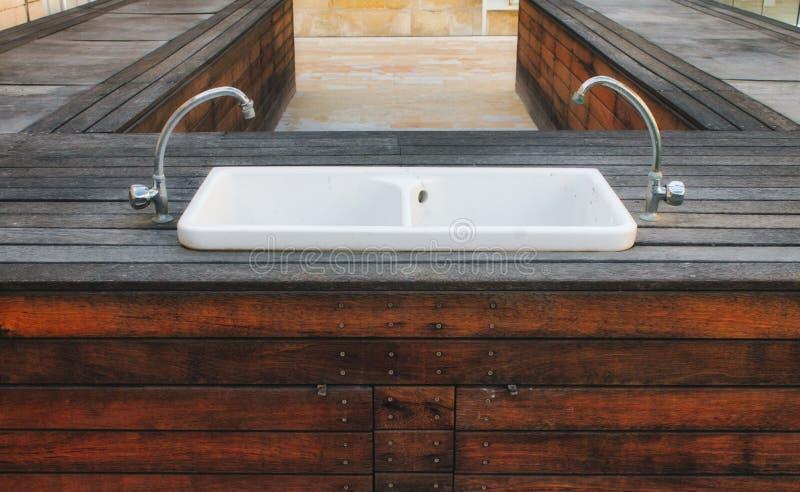 Lavabo de lavado a mano de la porcelana fijado en una plataforma de madera en un jardín elegante moderno imagen de archivo