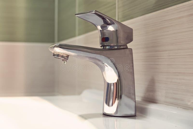lavabo de robinet de chrome A fermé l'eau d'égoutture de robinet dans la salle de bains Gaspillage de l'eau tendez le cou la coul photos stock