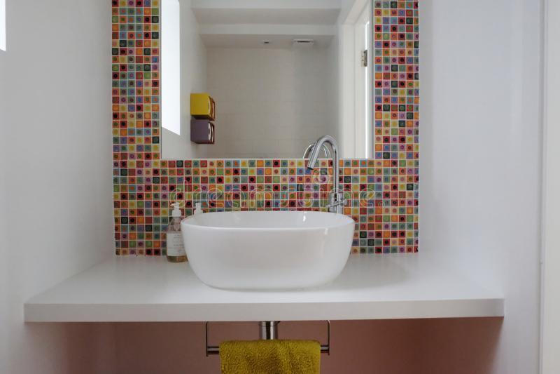 Lavabo de salle de bains avec les tuiles de mosaïque et l'encart en verre colorés de miroir dans les tuiles image libre de droits