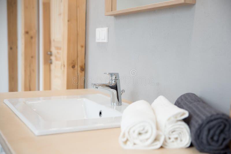 Lavabo ed asciugamani moderni bianchi nel bagno dell'hotel fotografie stock