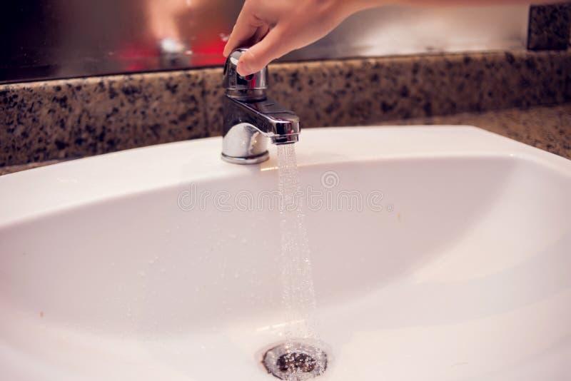 Lavabo ouvert de l'eau de robinet de chrome dans la salle de bains photo stock
