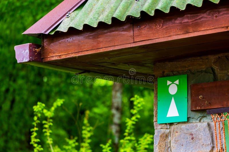 Lavabo p?blico Símbolo femenino blanco en fondo verde en muestra del retrete imagenes de archivo