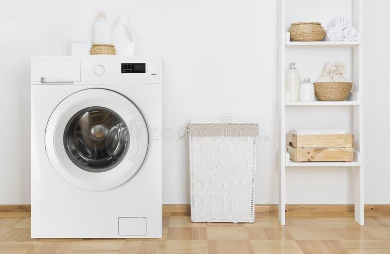 Lavadero interior con la lavadora y el estante cerca de la pared imágenes de archivo libres de regalías