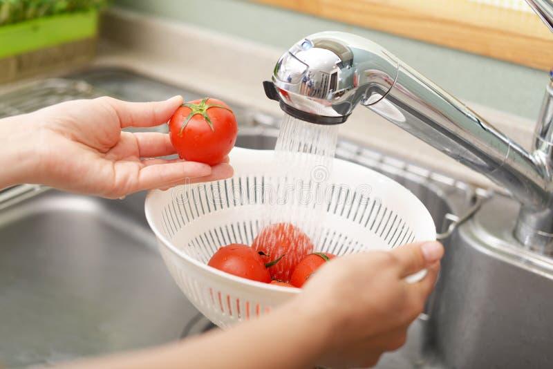 Lavado de la mujer los tomates foto de archivo