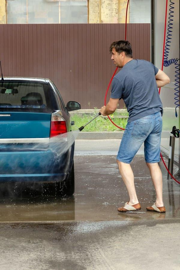Lavado del coche usando el agua de alta presi?n fotos de archivo