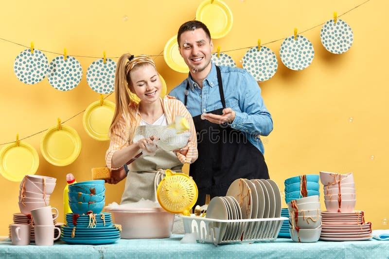 Lavado joven feliz de los pares en la cocina con la pared amarilla imagen de archivo
