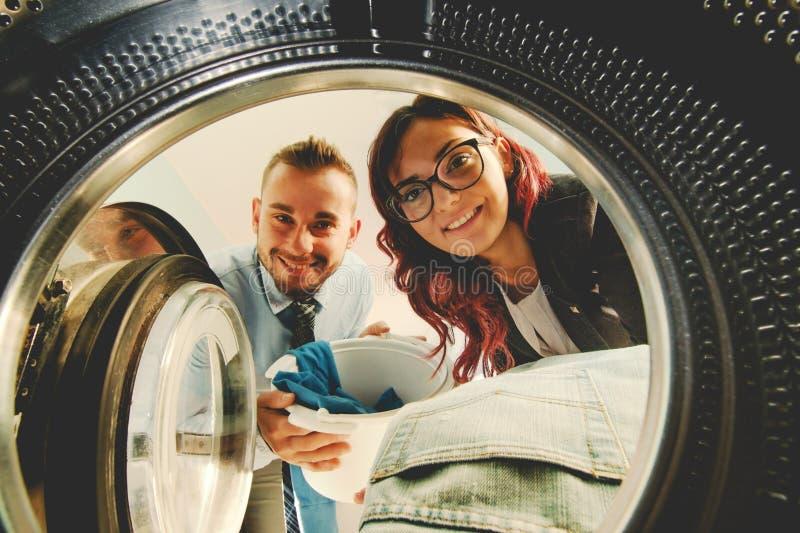 Lavadora cargada de los pares jovenes felices con la ropa vista de la lavadora imagen de archivo libre de regalías