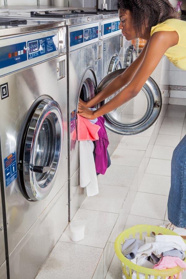 Lavadora del cargamento de la mujer con ropa imagen de archivo libre de regalías