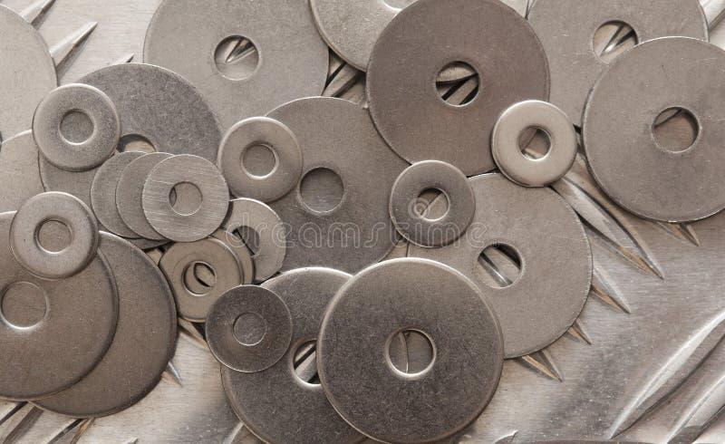 Lavadoras de metal dispersas numa grelha de aço não escorregada fotos de stock royalty free