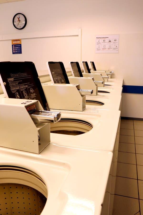 Lavadoras y ranuras de moneda en una lavandería imagen de archivo