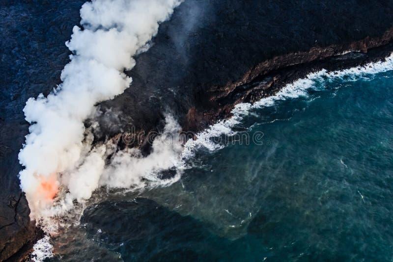 Lavaflöden in i kalla vattnet orsaka ånga och gaser till löneförhöjning I royaltyfri foto