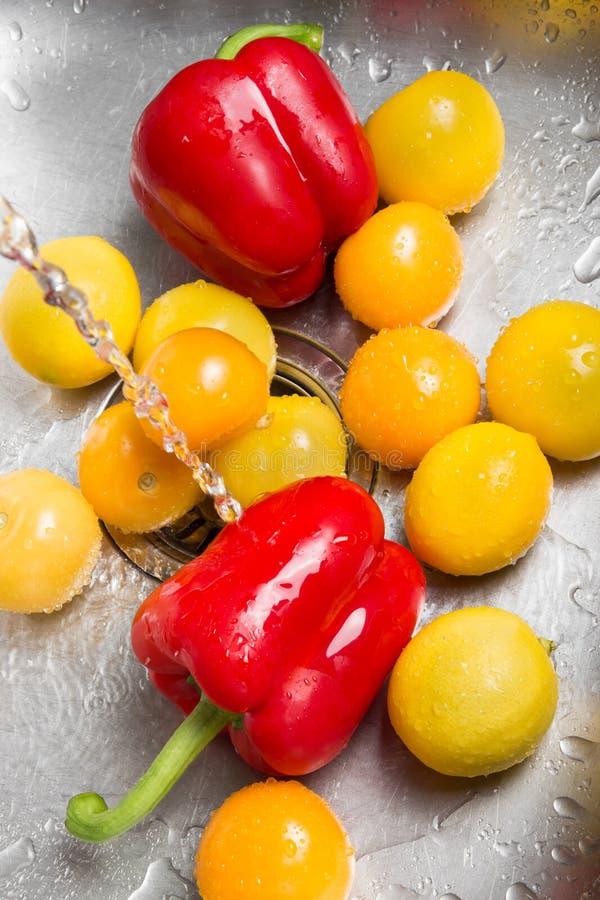 Lavage des fruits et légumes rouges et jaunes photos stock