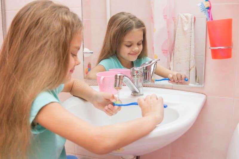 Lavagem da menina a escova de dentes sob água da torneira running imagem de stock