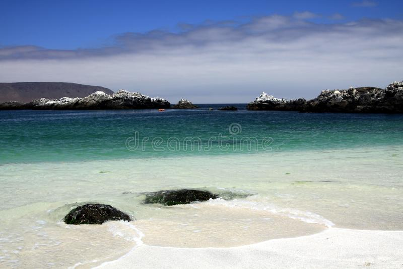 Lavagem da ressaca em volta dos pedregulhos pretos com a areia branca na associação natural de turquesa - Bahia Inglesa na Costa  imagem de stock