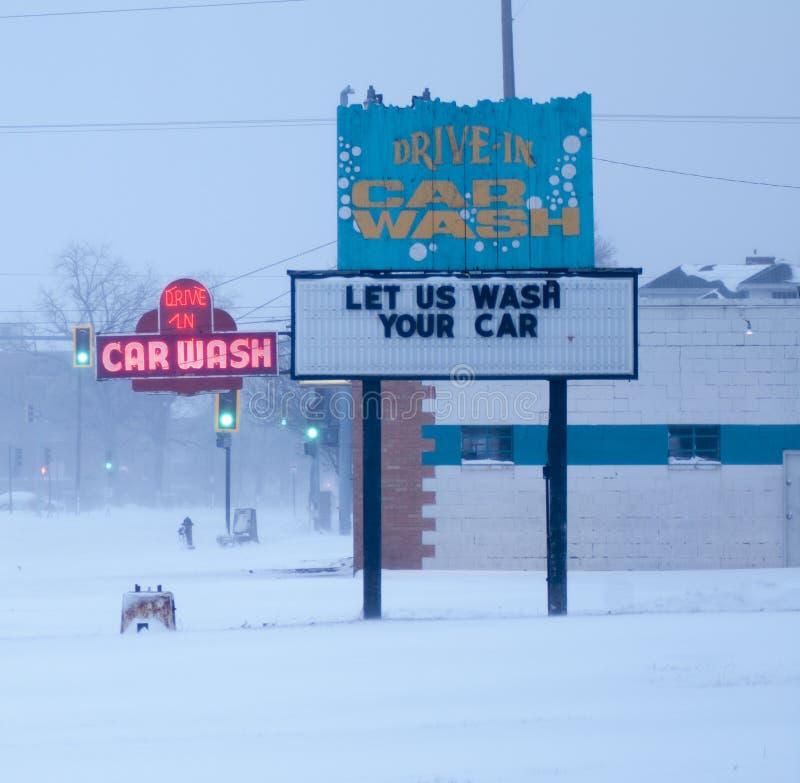 A lavagem de carros de néon assina dentro a tempestade da neve. imagens de stock royalty free