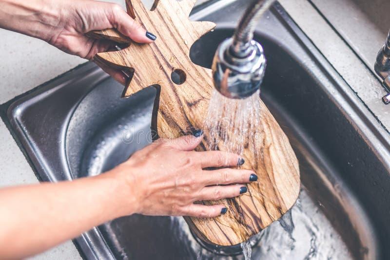 Lavagem de madeira da placa de corte da teca Mãos da mulher que lavam a placa de corte da teca imagem de stock royalty free