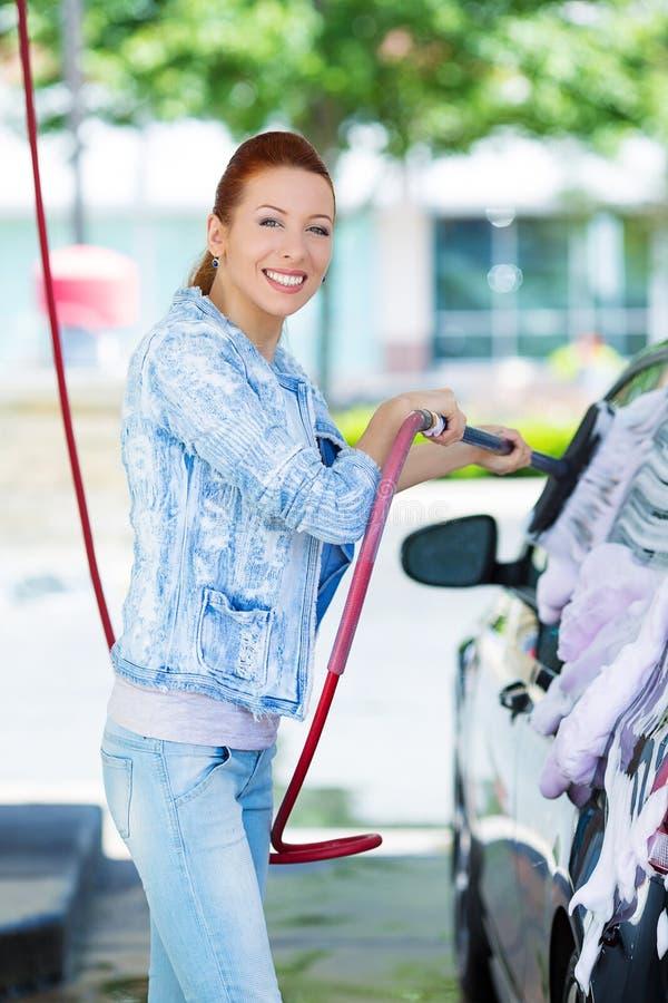 Lavagem de sorriso da jovem mulher, limpeza seu carro compacto fotografia de stock