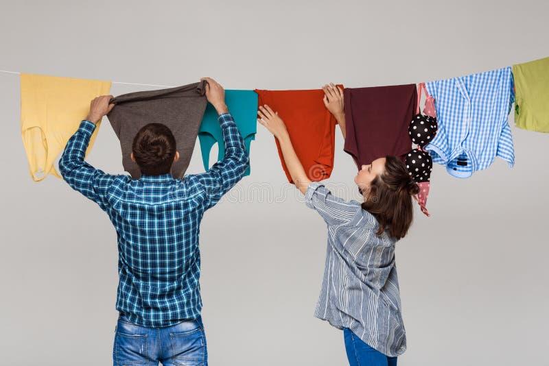 A lavagem de suspensão dos pares bonitos novos veste-se sobre o fundo cinzento fotografia de stock