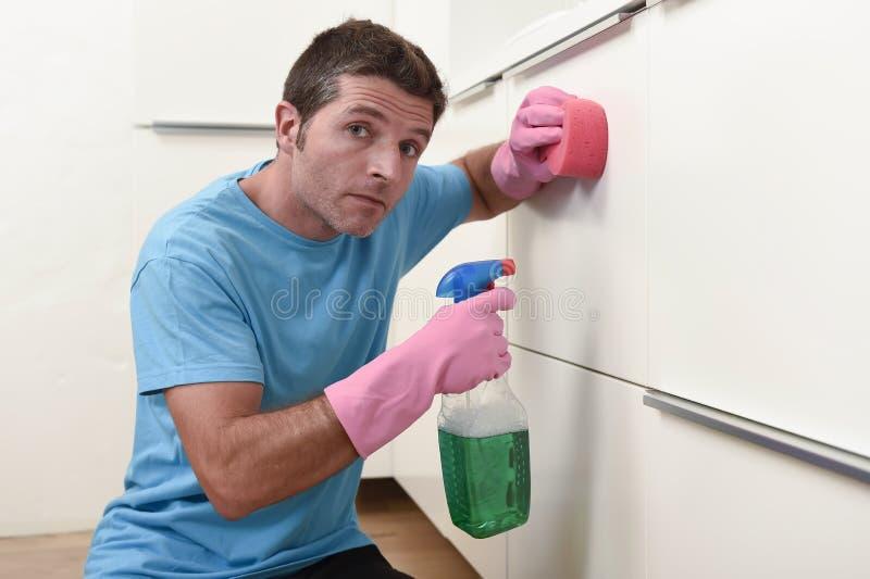 Lavagem e limpeza preguiçosas novas do homem do líquido de limpeza da casa a cozinha cansado no esforço foto de stock royalty free