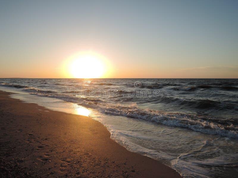 Lavagem macia das ondas de oceano do mar sobre o fundo dourado da areia Por do sol, nascer do sol, Sun fotografia de stock