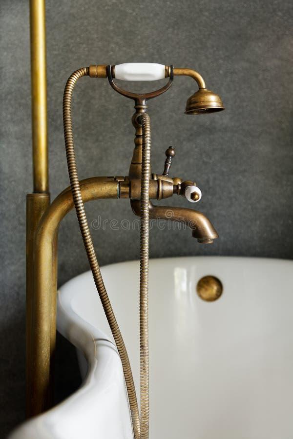 Lavagem ou torneira de bronze do vintage na banheira foto de stock