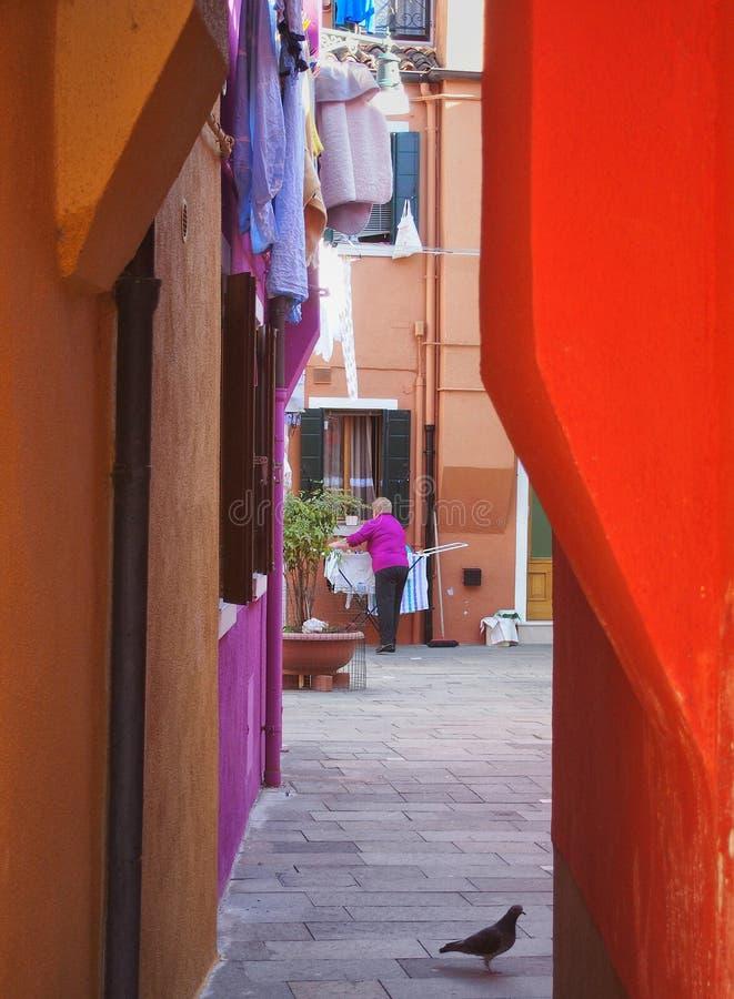 Lavaggio d'attaccatura della donna più anziana da asciugarsi in un cortile brillantemente colorato in burano Venezia fotografia stock