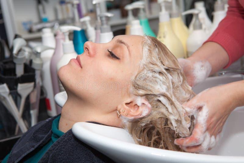 Lavaggio dei capelli ad un salone di lavoro di parrucchiere fotografie stock libere da diritti