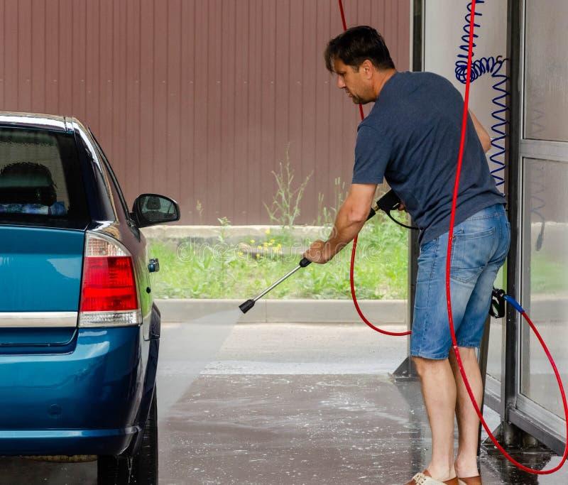 Lavaggio dell'automobile facendo uso dell'acqua ad alta pressione fotografia stock