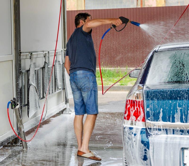 Lavaggio dell'automobile facendo uso dell'acqua ad alta pressione fotografie stock libere da diritti