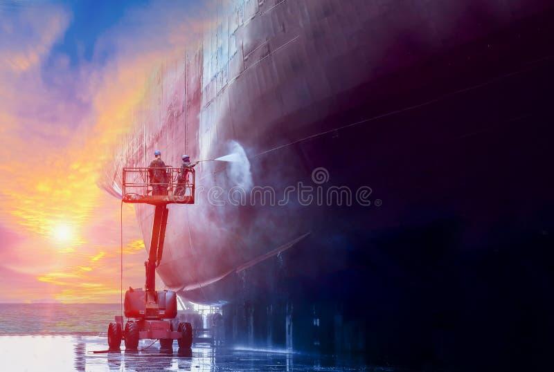 Lavaggio della nave di due lavoratori nel bacino galleggiante fotografie stock