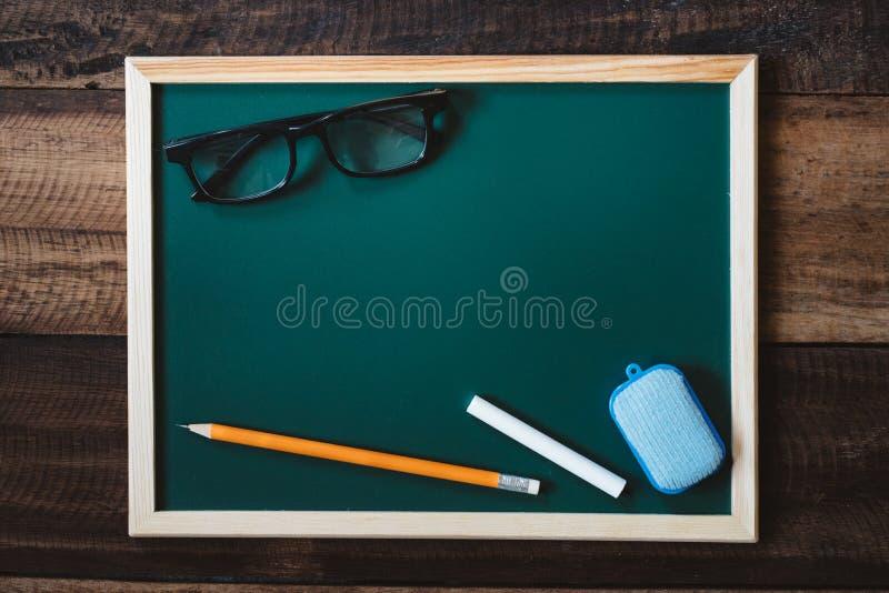 Lavagna in bianco con i vetri dell'occhio, la matita, il gesso bianco e lo spolveratore sulla tavola di legno fotografia stock libera da diritti