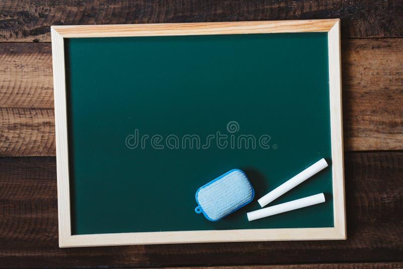 Lavagna in bianco con lo spolveratore e gesso bianco sulla tavola di legno immagine stock libera da diritti
