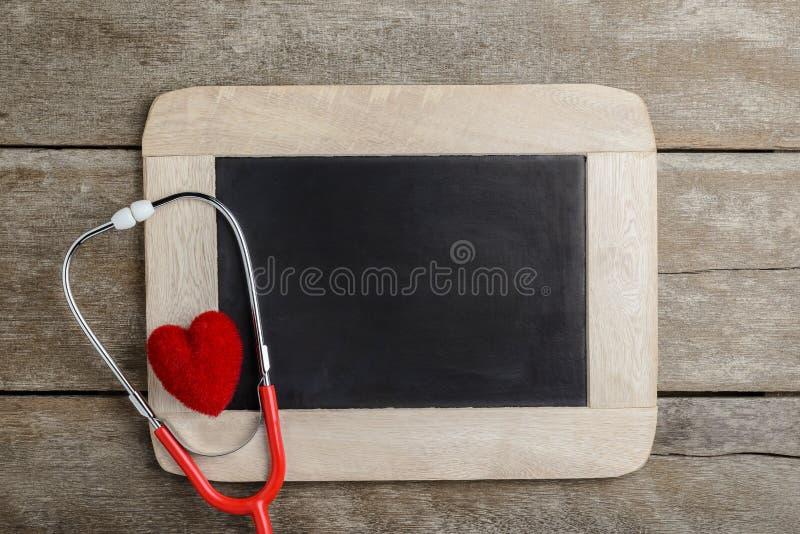 Lavagna in bianco, stetoscopio e cuore rosso, fondo c di salute fotografia stock