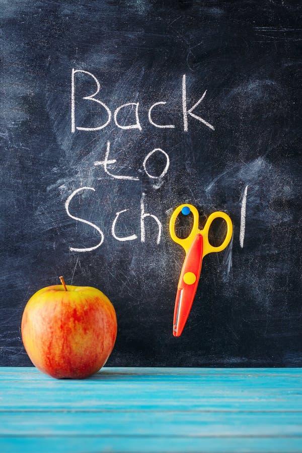 Lavagna con il ` dell'iscrizione di nuovo al `, alle forbici ed alla mela della scuola su fondo di legno blu fotografia stock libera da diritti