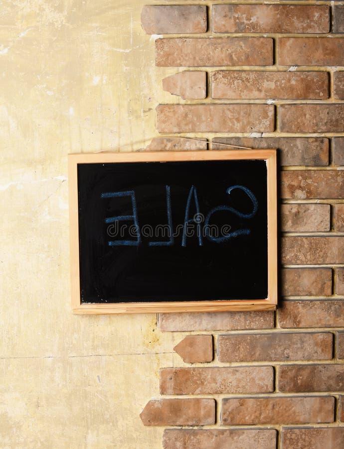 Lavagna con la vendita del testo nel telaio di legno sul fondo strutturato del muro di mattoni e del pastello fotografia stock