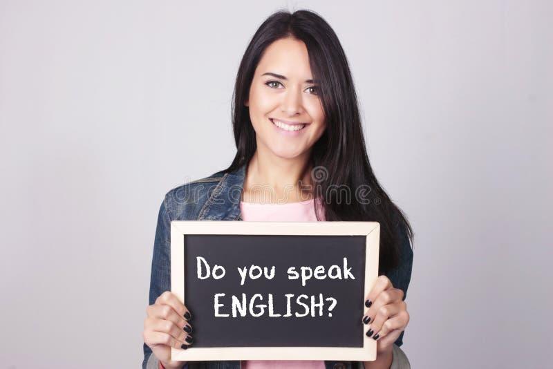 Lavagna della tenuta della giovane donna che dice parlate inglese? immagini stock libere da diritti