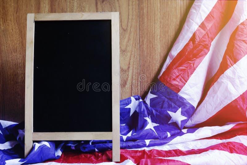 Lavagna e bandiera di U.S.A. sulla scena di legno della parete di Brown fotografia stock libera da diritti