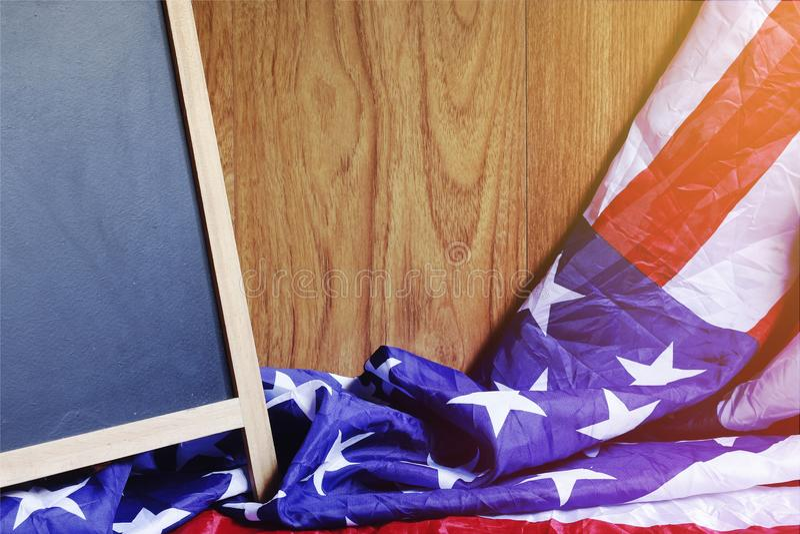 Lavagna e bandiera di U.S.A. sulla scena di legno della parete di Brown fotografia stock