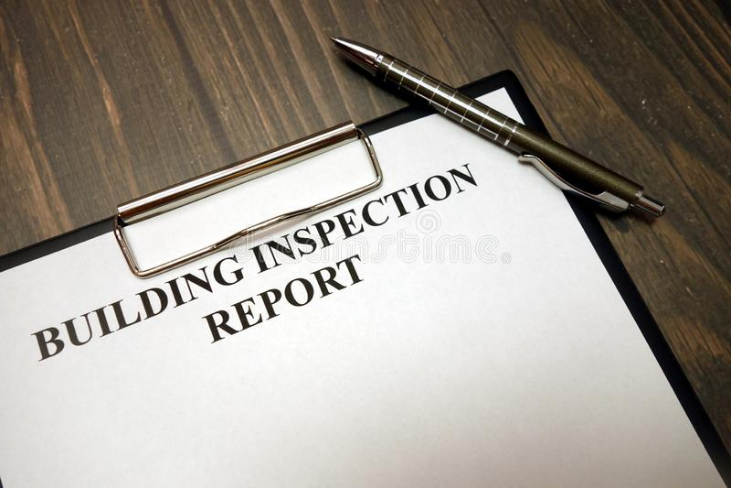 Lavagna per appunti con il rapporto d'ispezione di costruzione e penna sullo scrittorio immagini stock