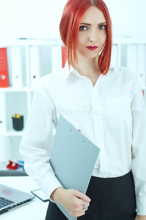Lavagna per appunti femminile della tenuta di segretario dei giovani rosso-capelli quando guardano diritto alla macchina fotograf immagini stock