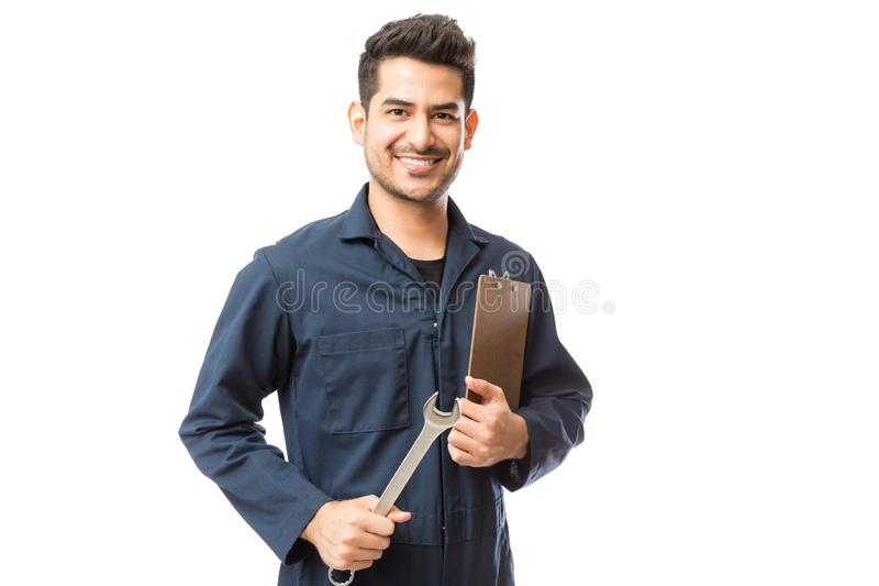 Lavagna per appunti maschio sorridente di Holding Wrench And del riparatore fotografia stock libera da diritti