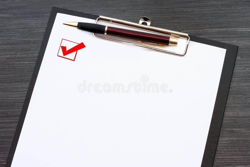 Lavagna per appunti nera con il foglio di carta bianco la penna del metallo ed isolata sulla tavola di legno scura Casella di con fotografia stock libera da diritti