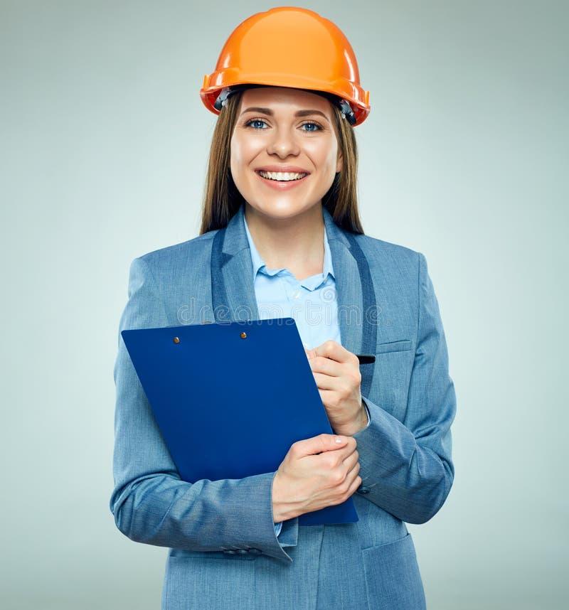 Lavagna per appunti sorridente della tenuta del costruttore della donna di affari con il contratto immagini stock