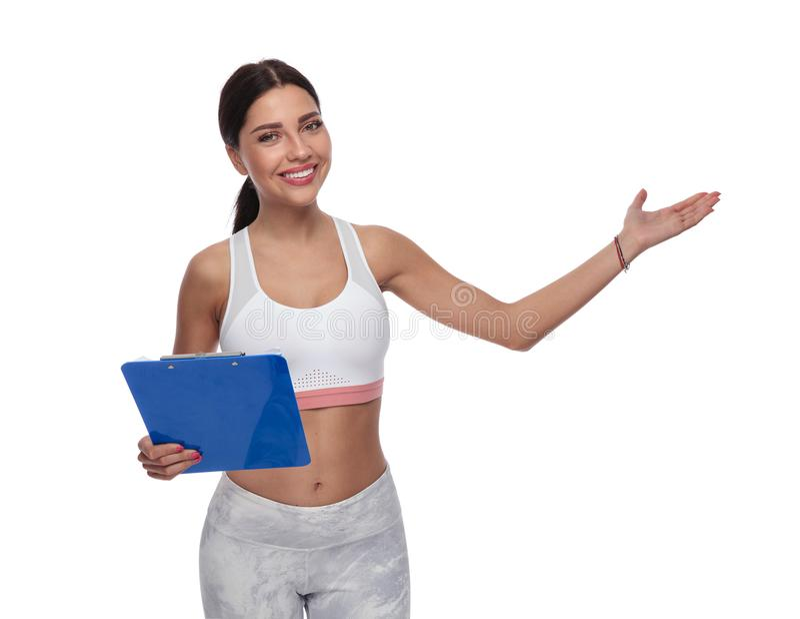 Lavagna per appunti sorridente della tenuta della donna di forma fisica e presentare al lato immagine stock