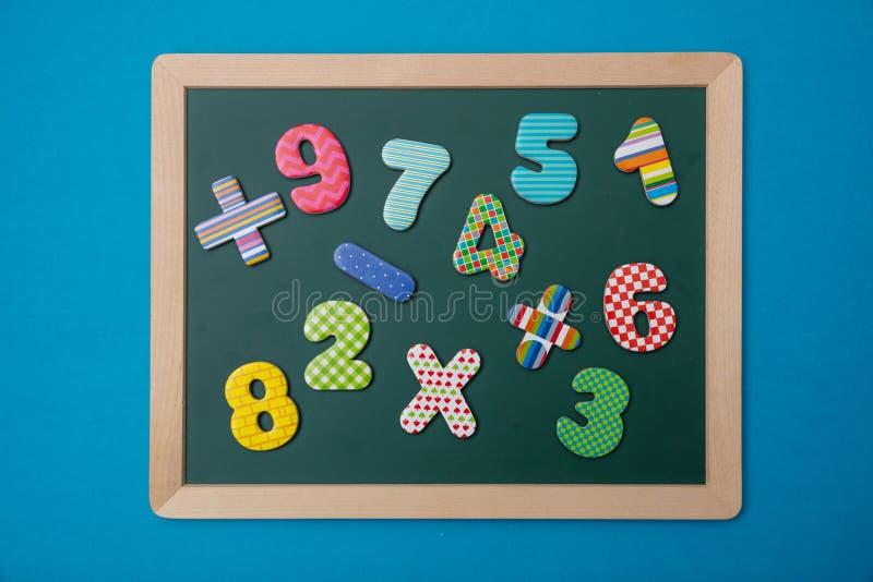 Lavagna verde con la struttura di legno, i segni variopinti di operazione di per la matematica ed i numeri, fondo blu immagine stock